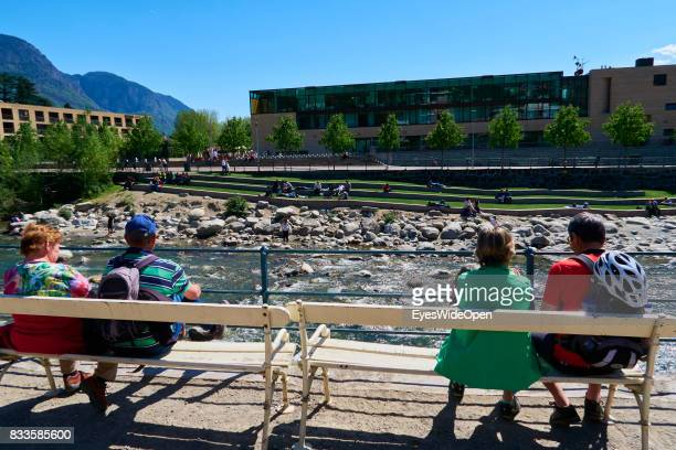 Tourists are enjoying the sun at the Etsch river in the green city centre of Meran in South Tyrol on April 21 2015 in Lana Italy
