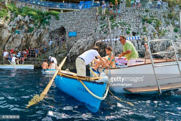 Tourists are entering small rowing boats to get into the Blue Grotto at the Island of Capri on June 24, 2015 in Naples, Italy.