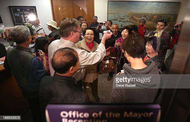 Tourists are greeted with magnets and a photo with the Mayor's receptionist as media wait for Mayor Rob Ford at City Hall in Toronto for him comment...