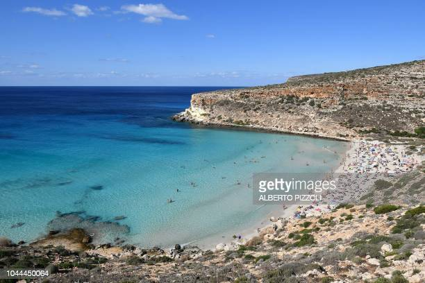 Tourists are pictured on the beach of the Isola dei Conigli in Lampedusa on September 27 2018 Five years after the worst shipwreck of its history the...