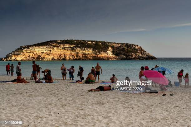 Tourists are pictured on the beach of the Isola dei Conigli in Lampedusa on September 25 2018 Five years after the worst shipwreck of its history the...