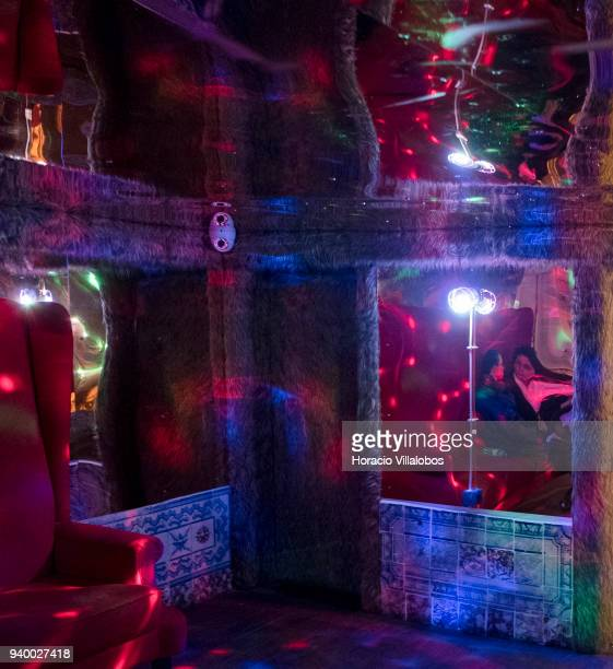 Tourists are reflected in walls and ceiling mirrors in a psychedelic room with a round couch at Pensao Amor a former brothel turned into a trendy bar...