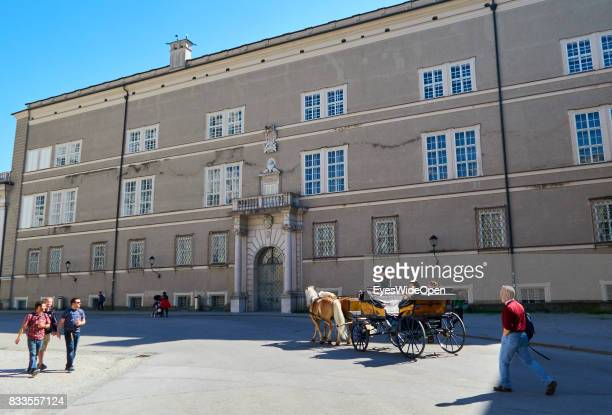 Tourists are riding with a horsedrawncarriage through the historic center on April 19 2015 in Salzburg Austria