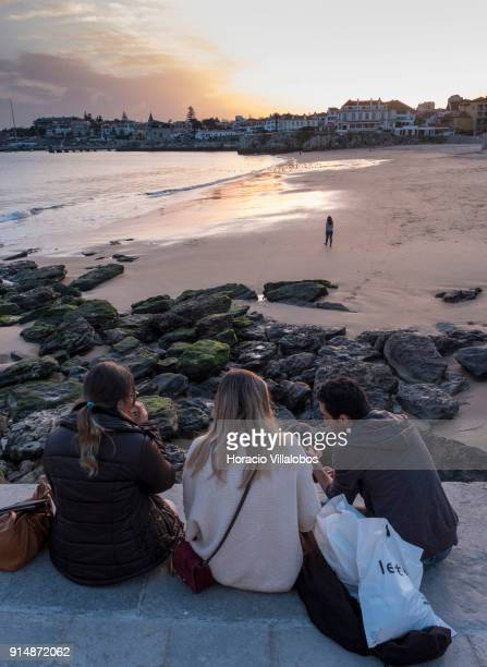 Tourists are seen at sunset while enjoying mild winter weather at Praia da Duquesa on January 30 2018 in Cascais Portugal Mild and sunny winter...