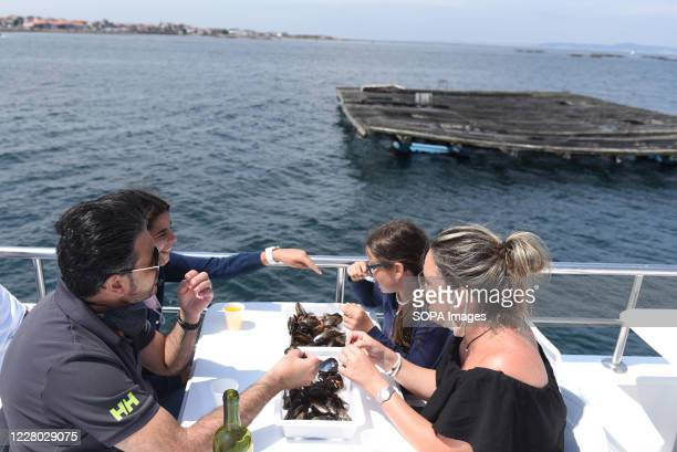 Tourists are seen eating mussels on a tourist boat near O Grove O Grove is a fishing village which is situated on the mouth of the Arousa estuary...