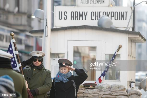 Tourists are seen having their picture taken on a cold morning on 13 February 2017 at checkpoint Charlie where formerly the border between the Soviet...