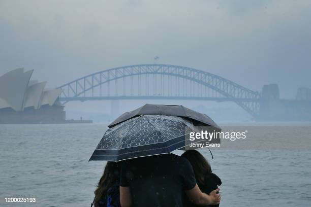 Tourists are seen looking at The Sydney Harbour Bridge in the rain on January 17 2020 in Sydney Australia A severe thunderstorm warning has been...