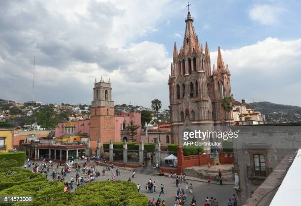 Tourists are seen on the main square in front of the San Miguel Arcangel cathedral on April 11 2017 in San Miguel de Allende Guanajuato state Mexico...