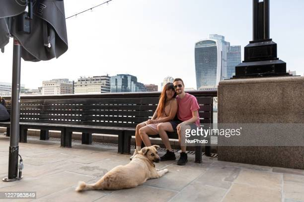 Tourists are seen relaxing on a boulevard at south bank of Thames river near London Bridge and City as London encourages internal tourism after...