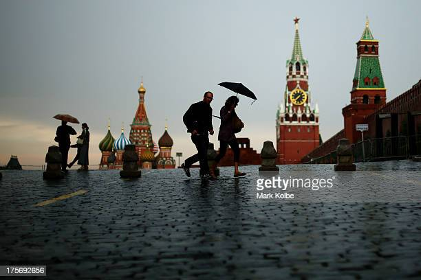 Tourists are seen running in the rain at Red Square ahead of the IAAF World Championships on August 5 2013 in Moscow Russia