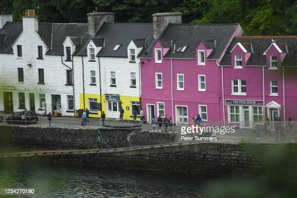 Tourists are seen sitting at the harbour on July 26, 2021 in Portree, Scotland. Skye and Raasay attracted 650,000 visitors in pre-covid 2019 with a...
