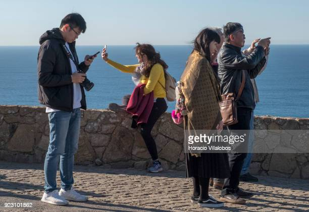 Tourists are seen taking selfies on a sunny winter afternoon in Cabo da Roca on February 22 2018 in Sintra Portugal Cabo da Roca is a cape which...