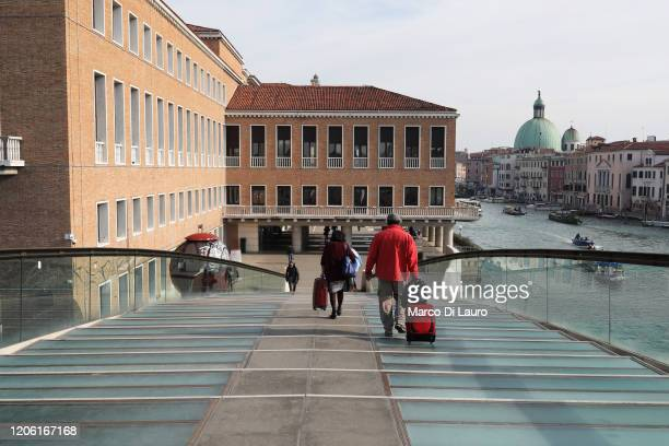 Tourists are seen with their luggage as they cross the Calatrava bridge towards the railway station as they try to leave a completely empty city on...