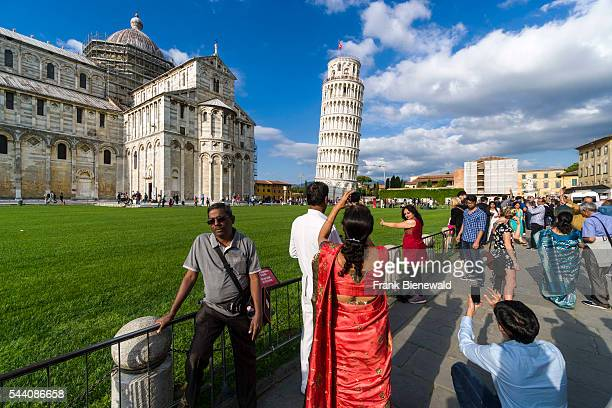 Tourists are taking photographs at Cathedral and Torre pendente di Pisa Leaning Tower