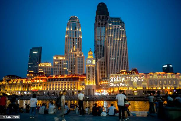 Tourists are viewing the night scene of Jinwan Plaza on the riverside Jinwan Plaza or Jinwan square located beside the Haihe river and opposite to...