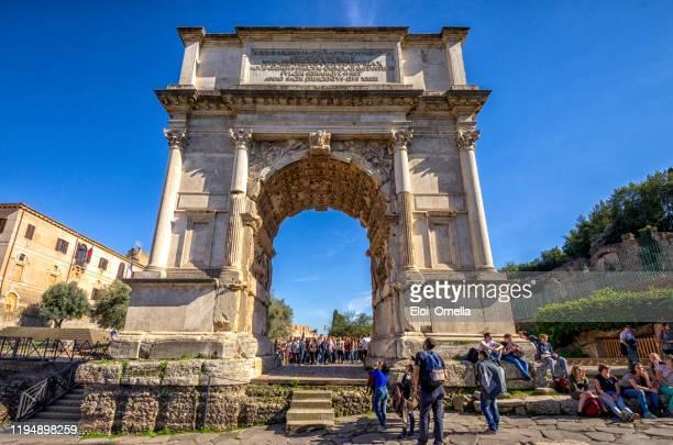 tourists are walking around arco di tito, rome, italy - roma itália imagens e fotografias de stock