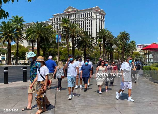 Tourists are wearing masks as they walk on the Strip in Las Vegas, Nevada, on August 28, 2020 amid the coronavirus pandemic.