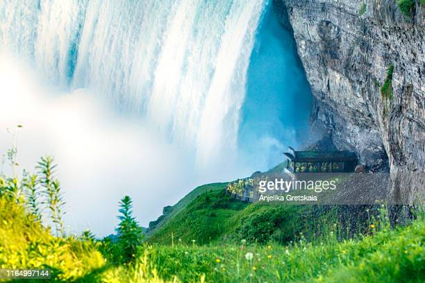 tourists are wearing yellow raincoats, are standing next to the beautiful horseshoe falls, niagara falls, ontario, canada - horseshoe falls niagara falls stock pictures, royalty-free photos & images