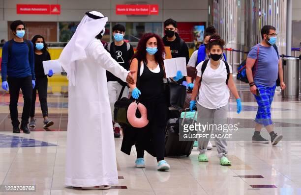 Tourists arrive at Dubai airport in the United Arab Emirates on July 8 as the country reopened its doors to international visitors in the hope of...