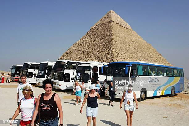 Tourists arrive by bus while Khafre pyramid looms behind November 13 2004 at Giza just outside Cairo Egypt The three large pyramids at Giza built by...