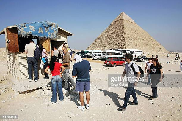 Tourists arrive to buy tickets while Khafre pyramid looms behind November 13 2004 at Giza just outside Cairo Egypt The three large pyramids at Giza...