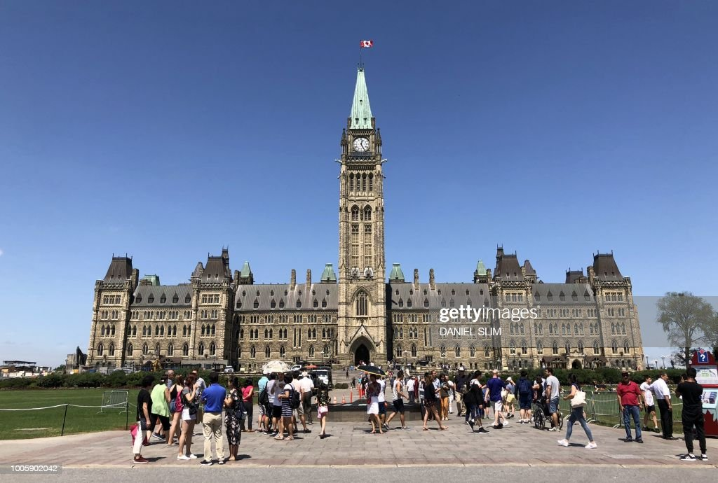 Tourists arrive to the front lawn of Parliament Hill, Ottawa