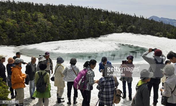 Tourists assemble around the Hachimantai Dragon's Eye a large area of ice surrounded by water at the Kagaminuma Pond near Mt Hachimantai's summit in...