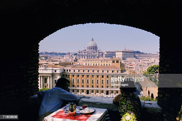Tourists at a dining table looking at a basilica, St. Peter's Basilica, Rome, Italy