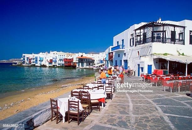 Tourists at a sidewalk cafe near a beach, Little Venice, Greece