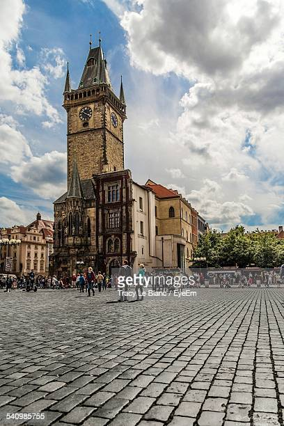 tourists at astronomical clock tower against cloudy sky - astronomical clock prague stock pictures, royalty-free photos & images