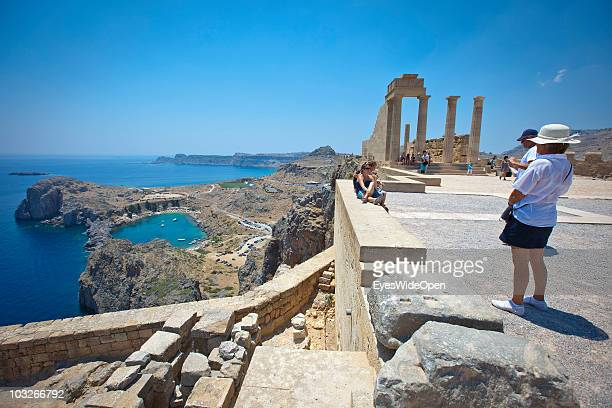 Tourists at AthenaLindiaTemple at the Acropolis of Lindos on July 04 2010 in Lindos Greece The old town of Lindos is famous for the ancient Acropolis...