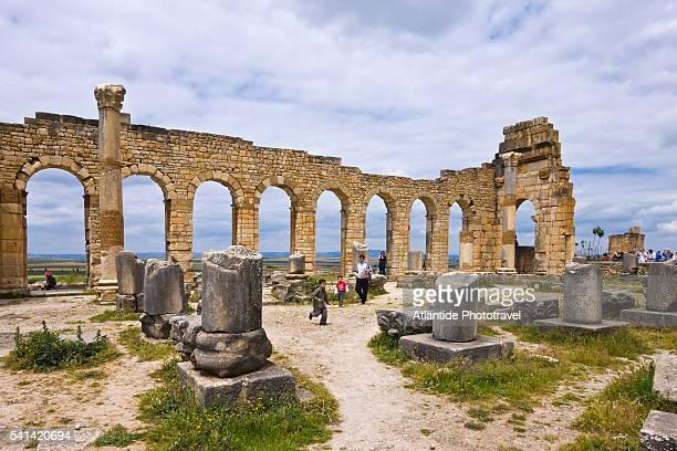 tourists at basilica of volubilis - volubilis fotografías e imágenes de stock