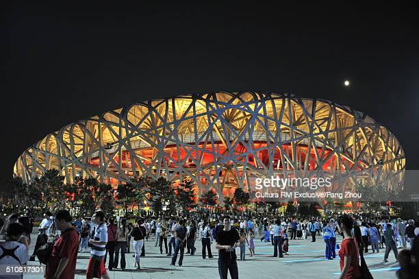 tourists at beijing national stadium (birds nest), olympic park square at night, beijing, china - nido de pájaro fotografías e imágenes de stock