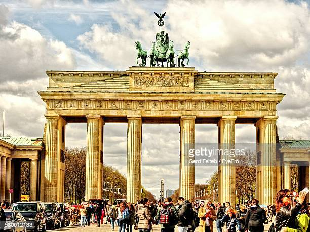 Tourists At Brandenburg Gate Against Cloudy Sky