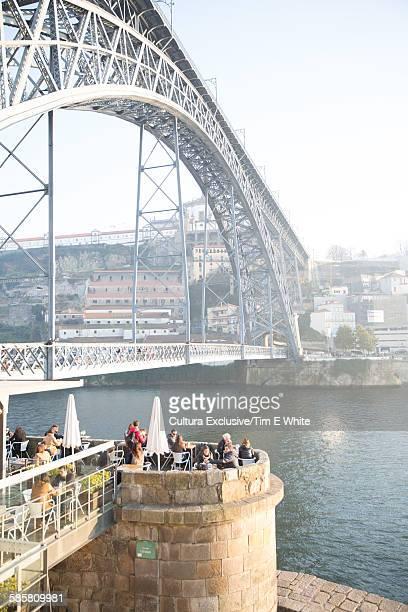 Tourists at bridge restaurant on riverside, Porto, Portugal