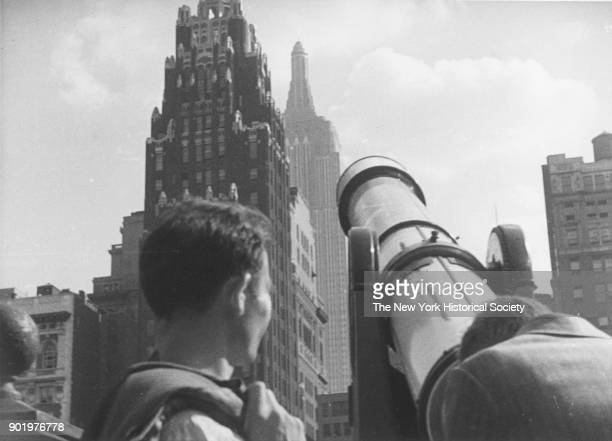 Tourists at Bryant Park looking through a telescope towards American Radiator Building Empire State Building New York New York 1929