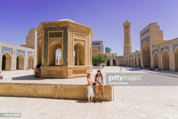 touristen am hof des kalyan moschee in buchara, usbekistan - allah stock-fotos und bilder