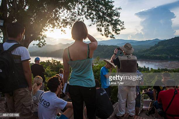 Tourists at Mount Phousi a 100m high hill with a Buddhist temple in the centre of the old town of Luang Prabang Climbing Mount Phousi also known as...