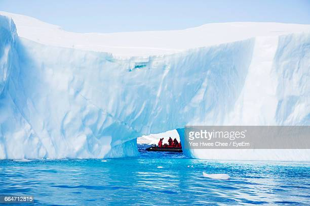 Tourists At Natural Ice Arch On Sea