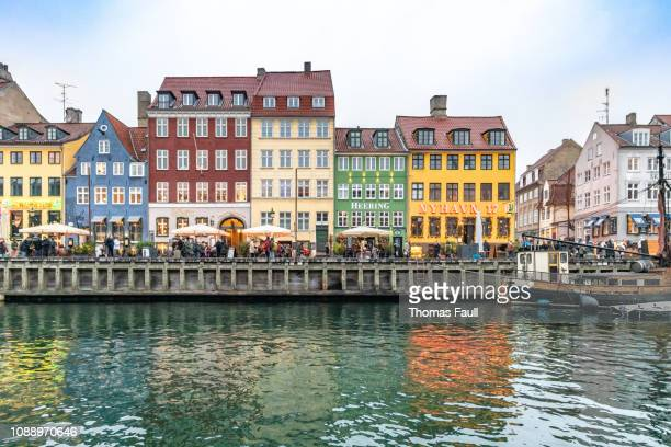 tourists at nyhavn harbour front in copenhagen, denmark - nyhavn stock pictures, royalty-free photos & images