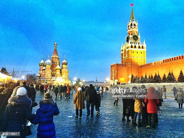 Tourists At Red Square By Illuminated Saint Basil Cathedral And Spasskaya Tower At Dusk