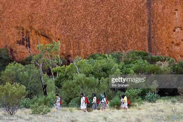 Tourists at the base of Ayers Rock Uluru Red Centre Australia