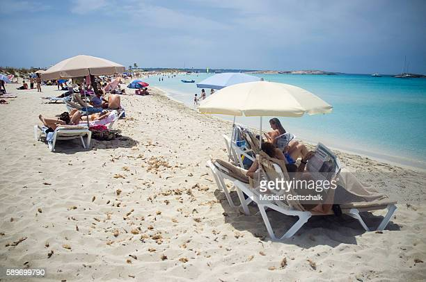Tourists at the beach at Playa de ses Illetes on Formentera island on May 12, 2016 in Formentera, Spain.