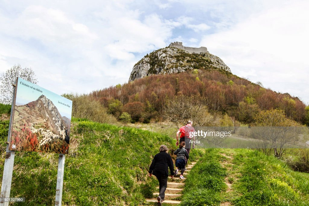Tourists at the bottom of the Montsegur Pog (rock formation). In the background, the Chateau de Montsegur, Cathar fortress, castle, registered as a National Historic Landmark (French 'Monument Historique').