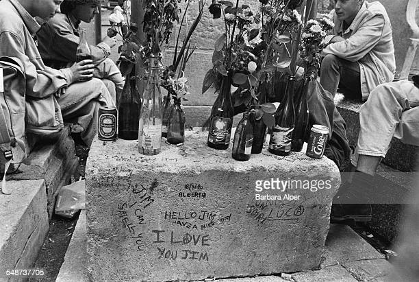 Tourists at the grave of American singer, Jim Morrison, in Père Lachaise Cemetery, Paris, France, July 1990.