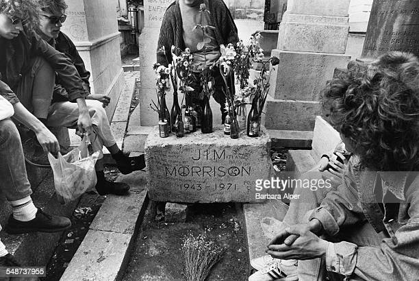 Tourists at the grave of American singer Jim Morrison in Père Lachaise Cemetery Paris France July 1990