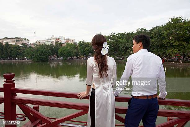 Tourists at the Hoan Kiem lake center of Hanoi A couple with the girl wearing a Vietnamese traditional dress called Ao Dai