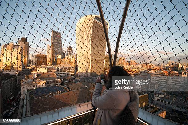 Tourists at the top of the Monument to the Great Fire of London look out and take pictures of the Walkie Talkie building as the sun sets on November...