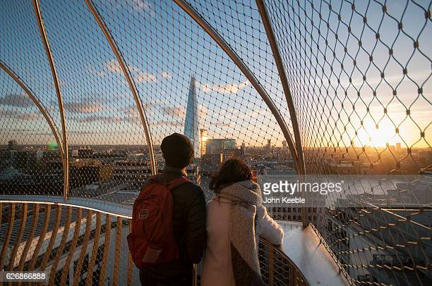 Tourists at the top of the Monument to the Great Fire of London look out toward the Shard building as the sun sets on November 28 in London United...