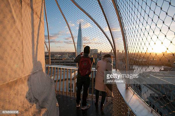 Tourists at the top of the Monument to the Great Fire of London look out and take pictures of the Shard building as the sun sets on November 28 in...